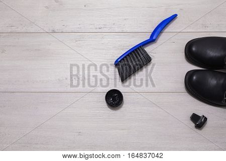 Black leather boots with shoe maintenance set on a wooden background.Brush for cleaning footwear .Formal business men leather shoes shining. Shoe polish on vintage surface