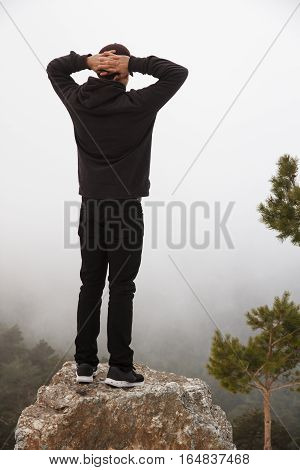 Handsome caucasian young man climbed up a rock in the mountain on a snowy day with foggy background - freedom, joy, goals, positivity, sport concept
