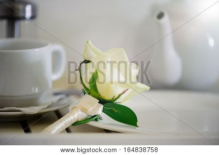 wedding boutonniere with white roses near the tea cups
