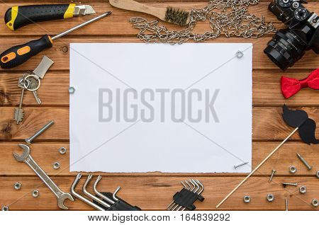 Father's Day flat lay mock up template with blank sheet of paper for greeting note and male accessories: tools, chain, photo camera, bow tie and funny photo booth paper mustache