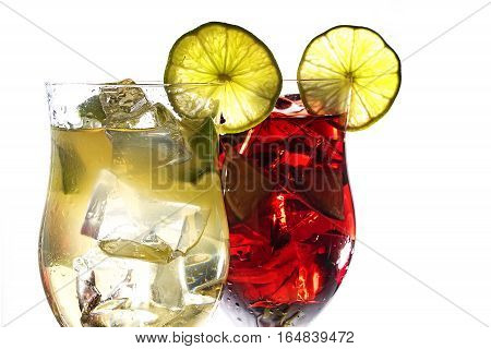 Two cocktail glasses green and red mixed drinks of juice berries lime and ice with or without alcohol isolated on a white background closeup selected focus narrow depth of field