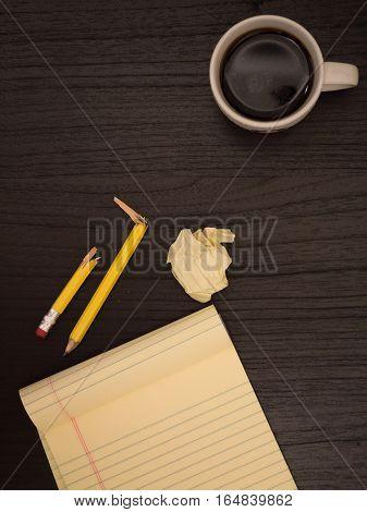 Dark surface yellow paper wads broken pencil coffee frustration