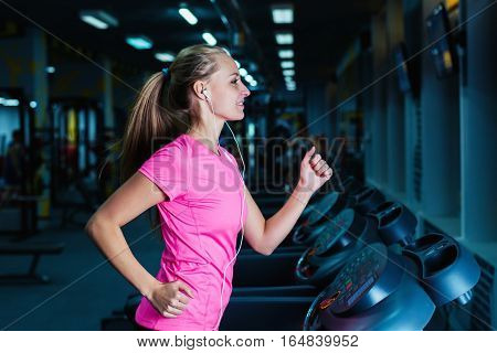 Attractive Fitness Girl Running On Machine Treadmill. Pretty Girl Doing Workout At Modern Fitness Gy