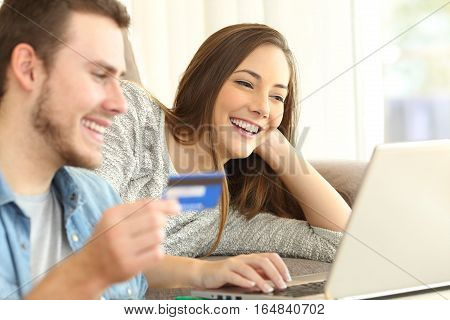 Close up of a happy couple buying on line with a credit card and a laptop on a couch in the living room at home