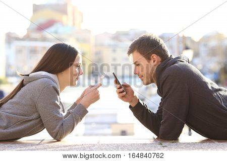 Side view of a couple of teens lying on the floor of a street and obsessed everyone with his smart phone and ignoring each other