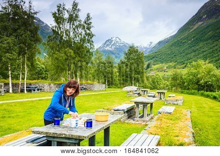Traveler woman have lunch on nature. Picnic site table and benches with view at norwegian mountains Scandinavia Europe.