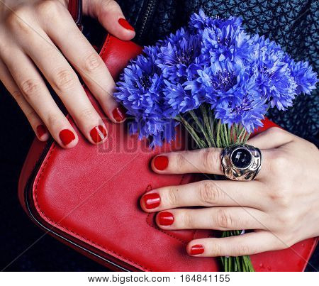 close up portrait of girls manicured hands holding small cute red handbag and cornflower bouquet, lifestyle concept beauty
