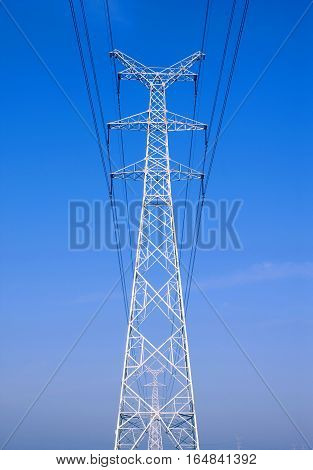 High voltage lines and power pylons on the sky