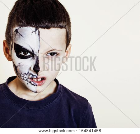 little cute boy with facepaint like skeleton to celebrate halloween or birthday party close up
