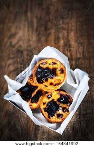 Typical portuguese dessert pasteis de nata in a white box on wooden background with copyspace / Heap of egg tarts