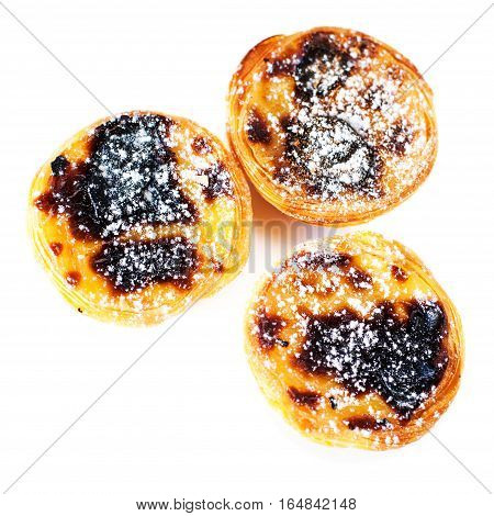 Typical portuguese dessert pasteis de nata / Heap of egg tarts isolated on white background close up