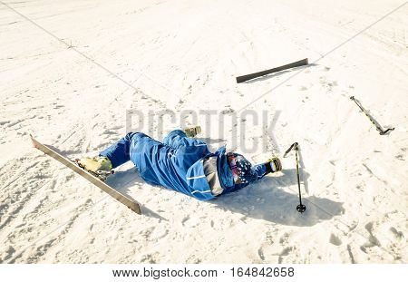 Professional skier after crash accident on skiing resort - Winter sport emergency concept with athlete needing help assistance on dramatic trouble situation - Warm sunny afternoon color tones