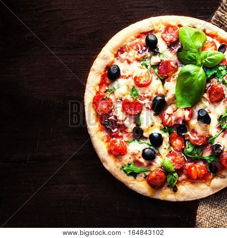 Hot pizza with Pepperoni Sausage on a dark background top view. Pizza on the black table with copy space.
