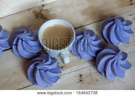 French blue meringue cookies and cup of coffee on white wooden background
