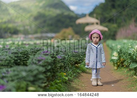 Little pretty cute toddler in the garden .