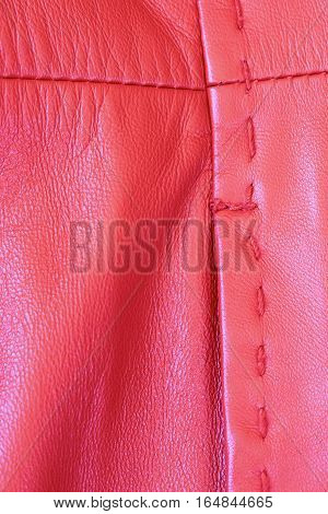 Stitching on the back of a bright red leather coat.