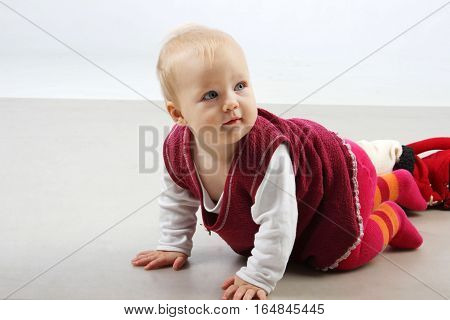 Adorable baby girl in red dress playing.