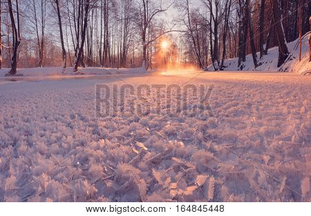 Winter sun shine on ice crystals. Background with ice patterns. Colorful winter backdrop. Close-up of Ice patterns in morning sunlight.