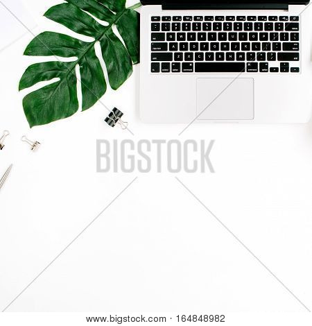 Home office workspace with laptop palm leaf and accessories. Flat lay top view
