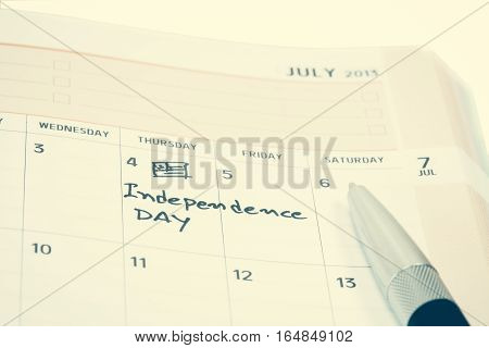 Hand writting word Independence day on calendar
