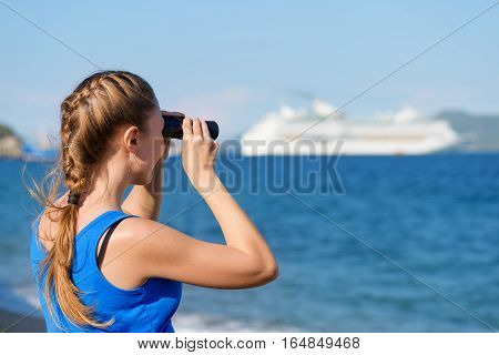 Young female tourist looking through binoculars at white cruise ship (liner) and enjoying beautiful sea view. Woman wearing blue dress. Her hair braided in French plait. Outdoor portrait in summer.