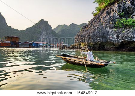 Woman In Boat Returns To Fishing Village. The Ha Long Bay