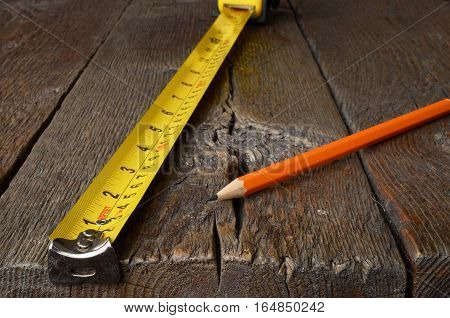 A close up image of a carpenters tape measure and one sharpened pencil.
