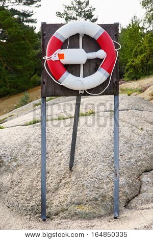 Lifebuoy in a rocky Norwegian coast mounted on a stand