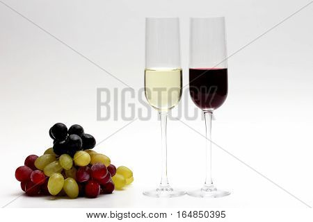 two glasses with red and white wine with grapes on a light background