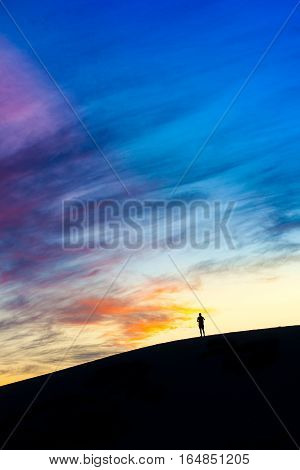 A man travelling alone silhouette in windy white sand dunes with dramatic twilight evening sky at Muine desert, Phan thiet, Vietnam
