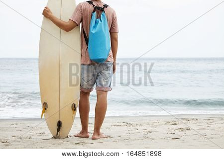 Tourism, Leisure And Healthy Lifestyle Concept. Back View Of Young Surfer Standing Barefooted On San