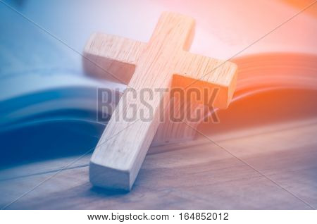 Closeup of simple wooden Christian cross necklace on Bible , vintage tone , god