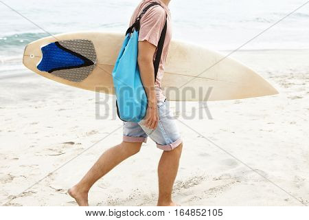 Cropped Shot Of Barefooted Man With Blue Bag Carrying White Surfboard In His Hand, Walking Along San