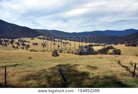 Broad panorama of the countryside in High Country Victoria with green field in foreground. Grassy hills near Dargo in Australia.