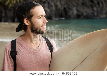 Hobby, Leisure And Adventure. Young Surfer With Cute Smile Carrying His Surf Board Under His Arm And