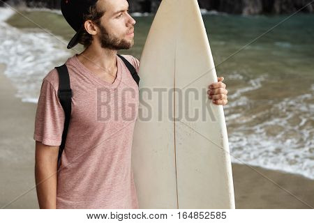Hobby, Watersports And Active Lifestyle Concept. Young Surfer Wearing Baseball Cap Backwards Standin