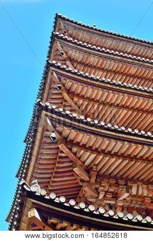 Five-storied pagoda roofs and blue sky at Daigoji temple Kyoto Japan.