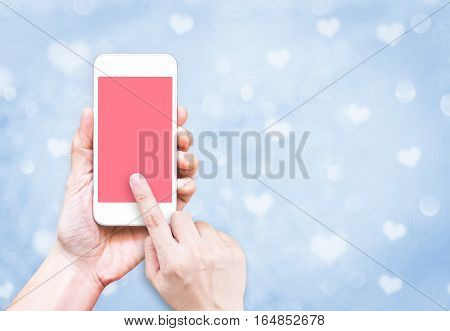 Hand Holding Mobile Phone With Finger Touch On Pink Screen On Blur Pastel  Blue Heart Bokeh Light Ba