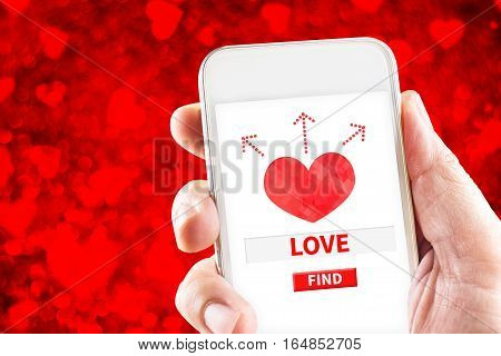 Close Up Hand Holding Mobile Phone With Search For Love And Heart On Screen With Blur Red Heart  Bok