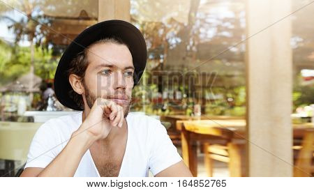 People, Leisure And Lifestyle Concept. Handsome Young Bearded Male In Headwear Holding Hand On His C