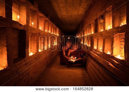 Young Buddhist Monk are reading a book with light from candle and sun light from outside to inside pagoda of old bagan with statue in mandalay historical park Bagan Mandalay Myanmar
