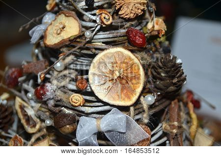 Christmas tree made of sticks fruits and berries. Handmade Christmas decoration background