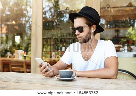 Attractive Young Male With Stubble Using Online App On His Cell Phone, Enjoying Free Wireless High S