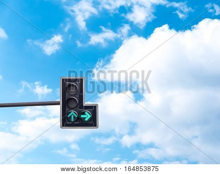 Green color on the traffic light with a beautiful blue sky in background Go straight and turn right