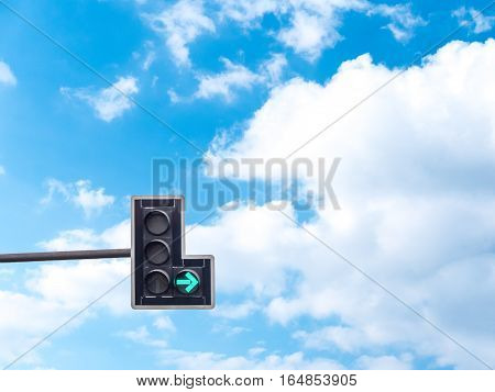Green color on the traffic light with a beautiful blue sky in background turn right