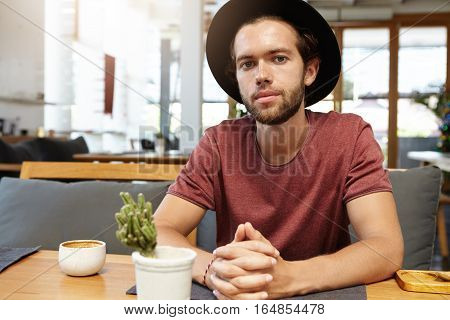 Fashionable Young Entrepreneur Wearing T-shirt And Trendy Black Hat Sitting At Wooden Table With Mug
