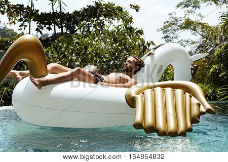 Holidays And Relaxation Concept. Young Caucasian Man With Fit Body Relaxing On Inflatable Mattress I