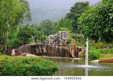 beautiful place with lots of greenery, beautiful views of the waterfall flowing over the stones, mountains covered with greenery and a pond, a Bush blooming orange flowers