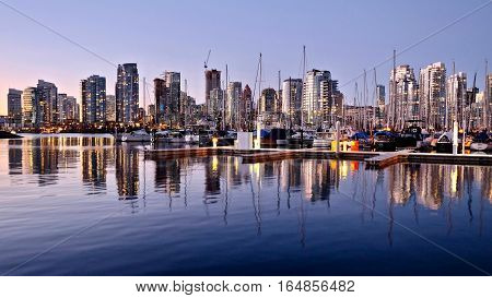 Civic Marina at sunset. City  reflection in False Creek and Yaletown. View from Kitsilano seawall. Vancouver. British Columbia. Canada.