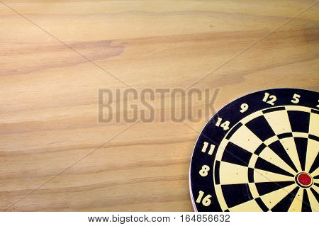 A Dart Board on a Wood Background